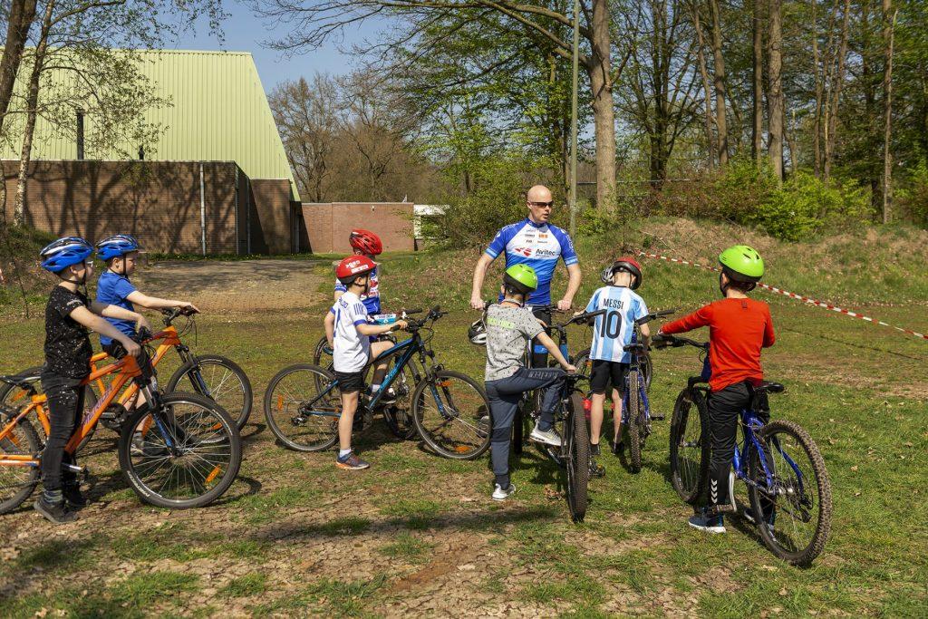 FotoEen begeleider legt een aantal jeugdige deelnemers aan de mtb-clinic op het sportpark 't Grootveld uit wat ze gaan doen; april 2019.