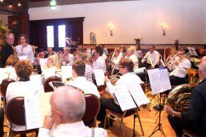 foto van de muzikanten van harmonieorkest De Volharding tijdens hun concert in zaal Cornelis in april 2019.