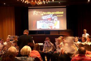 Foto van het concert van het harmonieorkest De Volharding in april 2019 in zaal Cornelis met op de achtergrond een scherm dat beelden vertoont van de film waarvan muziek wordt gespeeld.