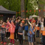 Foto van groep zingende kinderen op het marktplein in Dalen op koningsdag 2019.