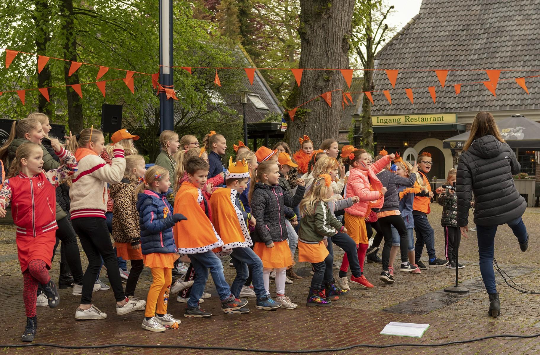 """Foto van zingende kinderen onder leiding van enthousiaste """"dirigente""""op koningsdag 2019 op het marktplein in Dalen."""