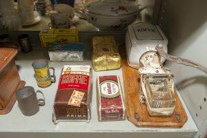 Foto Een wandkoffiemolen uit de de jaren 60/70 van de vorige eeuw, met verschillende soorten koffiebonen zoals Van Nelle en Prima. Ook liggen er nog pakjes thee van bijvoorbeeld het merk Tiktak.