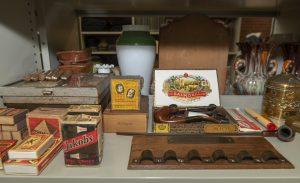 Foto Een foto van pijpen en een pijpenrek, sigaren en tabakswaren en lucifers uit vroeger tijden.