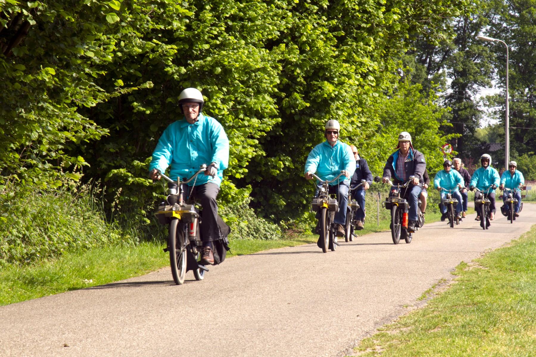 Foto van aantal deelnemers aan de toerrit van de solexclub De Reutel; allemaal geskleed in het lichtblauwe jasje van de club.