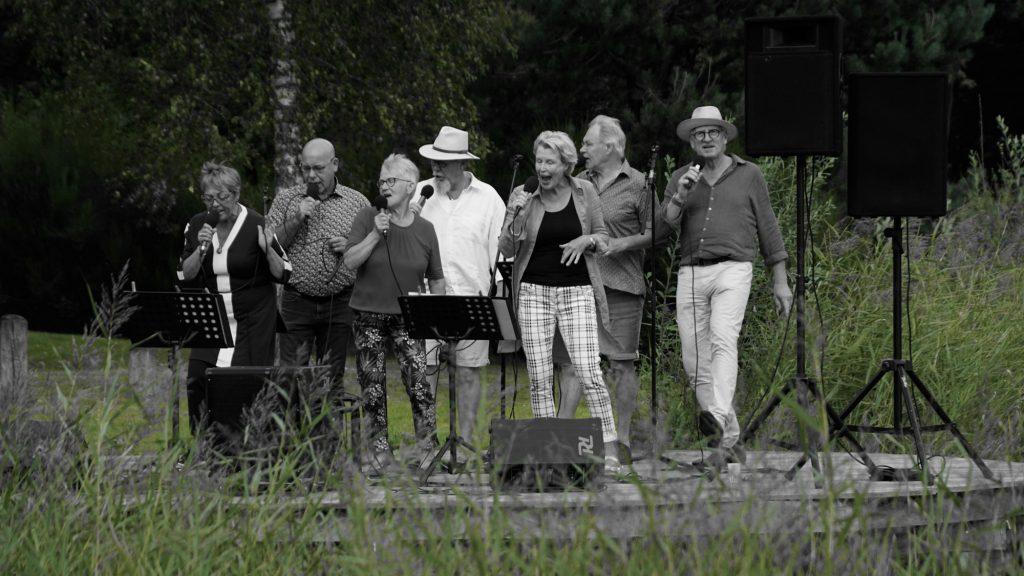 """Een zwart/wit foto van de zangeressen en de zangers van de popzanggroep """"Van 10 tot 12"""", tijdens een optreden in de Daoler Tuun in september 2019."""