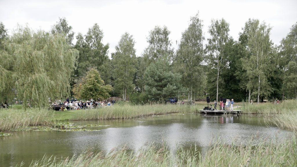 """Overzichtsfoto van een deel van de Daoler Tuun, tijdens het optreden van de popzanggroep """"Van 10 tot 12"""", met daarop op de voorgrond de waterpartij en op de achtergrond een deel van het publiek en de de popzanggroep."""