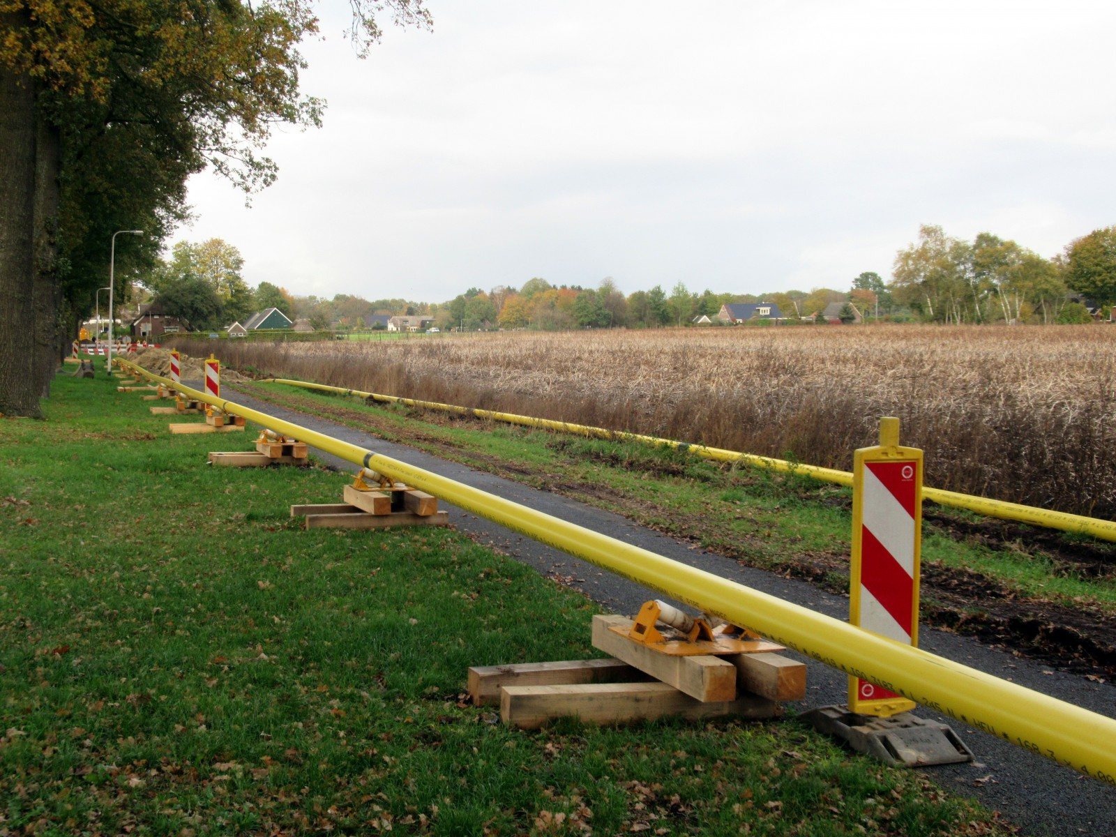 Foto van de geel gekleurde gasbuizen langs het fietspad Coevorden naar Dalen, klaar voor het in de grondleggen.