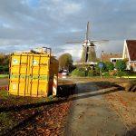 Foto van een gele container die aan de Bente is geplaatst voor vervanging van de gasleiding aan de Bente; op de achtergrond de Bentermolen.